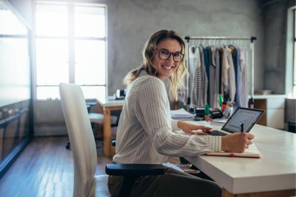 Una donna sorridente lavora alla sua scrivania con il pc